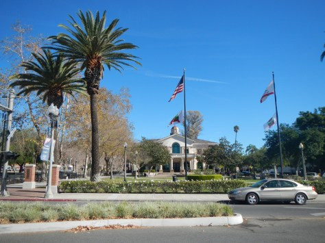 The central park in Fillmore is lined with palm trees and backed by old railroad trains.