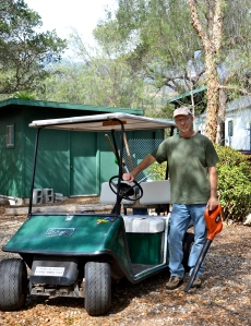 The golf cart is loaded with tools for the tasks.