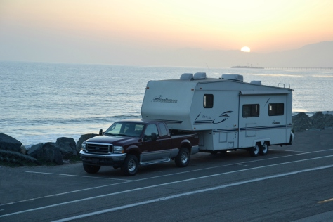 The sun sets over the RV on the shore at Seacliff, California.