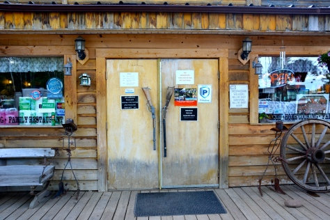 The western saloon-themed RV park at Fort Nelson, BC, had chainsaw-carved benches and rifles for door pulls.