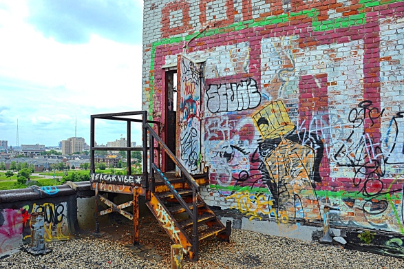 Graffiti artists have left large and intricate murals on the wall of the rooftop access room.