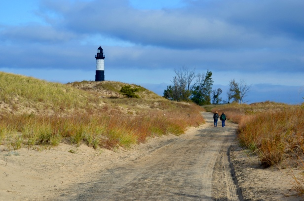 The lighthouse is at the end of a service lane through the dunes.