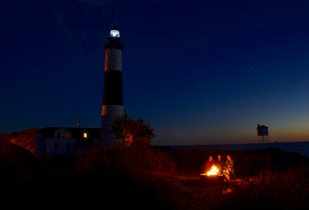 Workers enjoy a twilight campfire on the sand dunes next to the lighthouse.