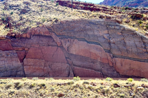 Rock strata have slipped several feet along the Moab Fault made visible by the rock cut for highway 191 across from the park entrance.